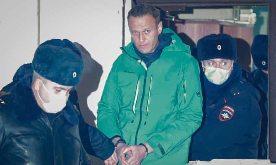 Russian opposition leader and anti-corruption activist Alexei Navalny (centre) is escorted out of a police station in Khimki outside Moscow, Russia