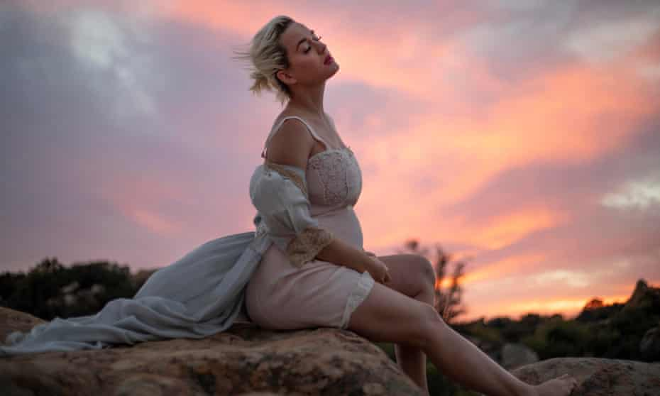 Katy Perry pregnant sitting on a rock at sunset