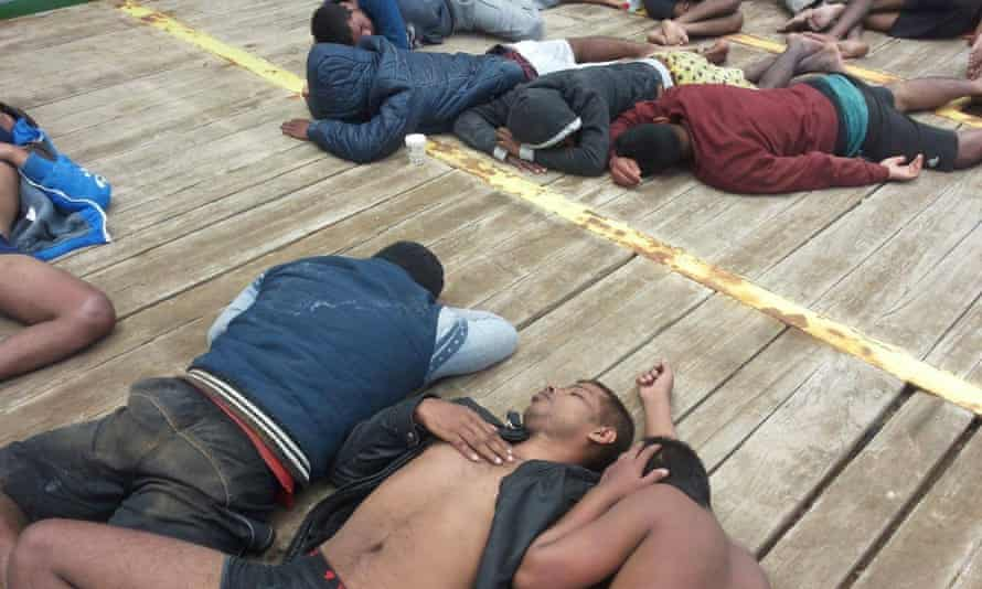 Migrants sleep on the deck of the Maridive 601, the Egyptian tugboat that rescued them only to be denied permission to land for almost three weeks
