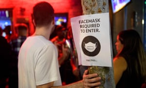 Face mask signage is seen outside a bar in West Hollywood, California.