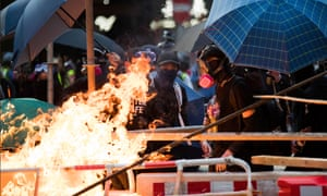 Hundreds of thousands defy Hong Kong's protest ban, as police fire water canon with dye and pepper solution in busy shopping thoroughfare.