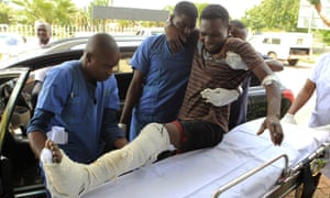 An injured man is helped at a private hospital in Harare