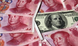 A US $100 banknote is placed next to 100-yuan banknotes