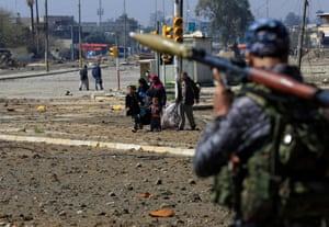A displaced Iraqi family escape from clashes during a battle between Iraqi forces and Islamic State