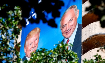 Israeli Likud party election banners hang from a building, showing Benjamin Netanyahu shaking hands with Donald Trump, in Tel Aviv.