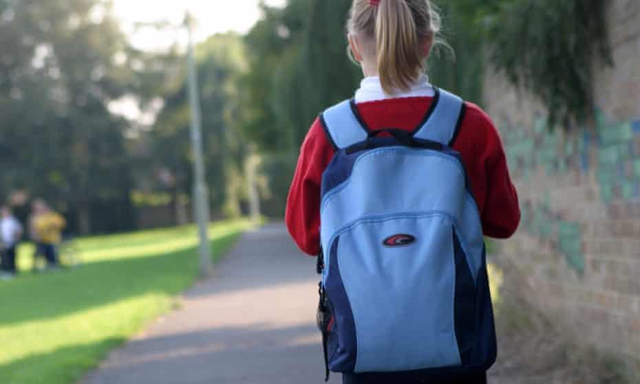 Girl in school uniform and backpack walking in park