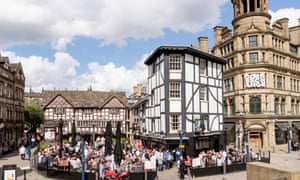 16th century timbered The Old Wellington Inn 1552 with crowds of people in beer garden. Manchester