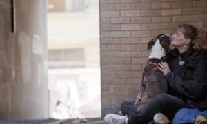 Woman with dog sitting on street corner