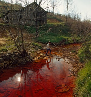 Boy walks across polluted stream which runs by weathered barn on hill, Near Berea, Kentucky
