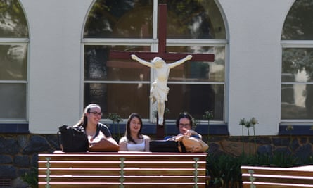 Students sit under a statue of Christ at the Australian Catholic University in Canberra