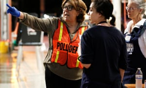 A poll worker wearing protective gloves speaks with fellow workers during the Democratic presidential primary election at a polling center inside a fire station in the Coral Gables neighbourhood in Miami, Florida, today.