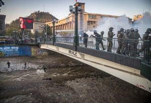 A youth lies in the Mapocho river after being bundled over the railings of the bridge by a police officer.