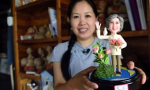 Chinese artist Wu Xiaoli with a model of prime minister Theresa May for the G20 summit