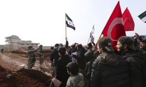 Syrians meet Turkish troops outside their base near the village of Binish, in Idlib province. Turkey, backer of Syria's opposition, has been deploying equipment and troops in the region, to halt the Syrian military's advances.
