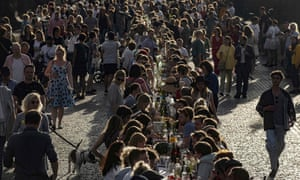 People walk past and sit at a half-kilometre long table set up on the Charles Bridge in Prague