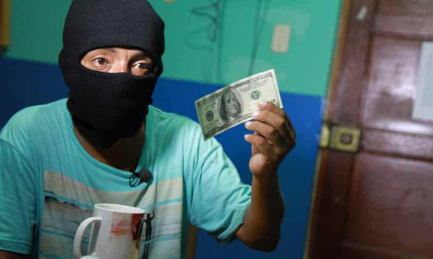A Peruvian counterfeiter demonstrates the finishing touches to a fake bill.