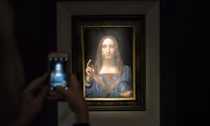 A visitor takes a photo of the painting Salvator Mundi by Leonardo da Vinci at Christie's New York auction house.