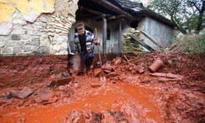 A man tries to clean up his house following the spill