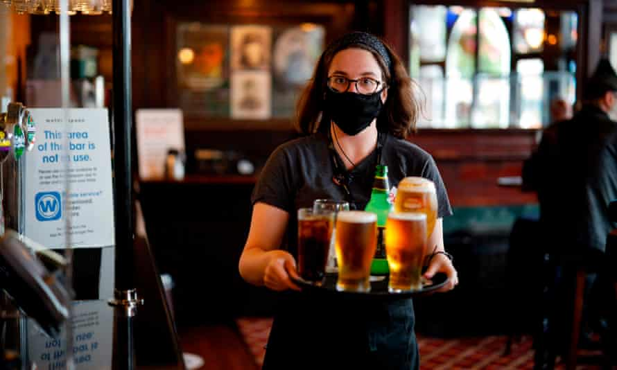 A member of staff wearing a face mask carries drinks inside a pub