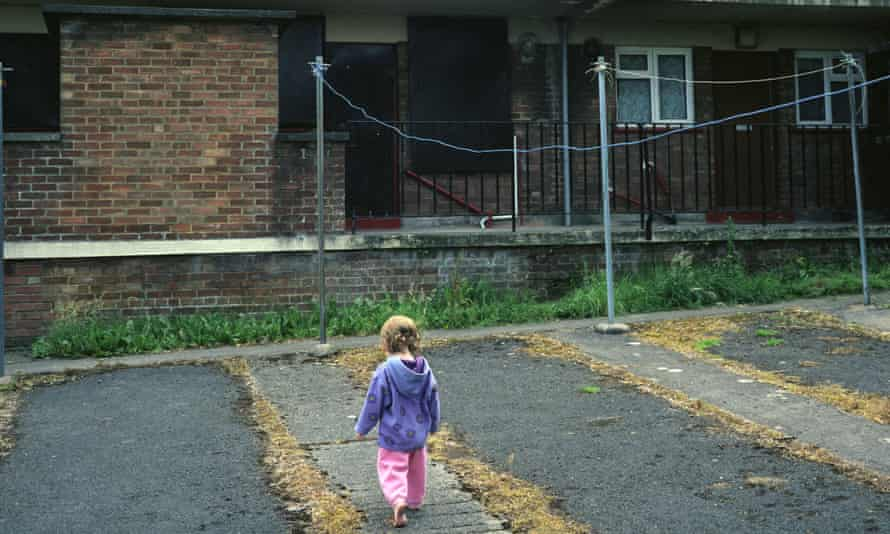 a young child plays on the concrete outside a block of flats on a council estate