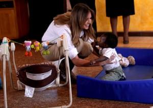 Trump picks up a toddler at the Nairobi children's home.