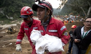 A fireman carries the body of a child from the landslide in Cambray in the suburb of Santa Catarina Pinula, about 10 miles east of Guatemala City on Friday.