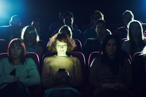 Woman on mobile phone in cinema