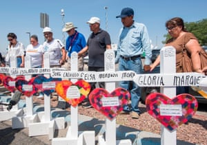 People pray beside crosses with the names of victims of the shooting that left 22 people dead at the Cielo Vista Mall WalMart in El Paso, Texas, on 5 August 2019