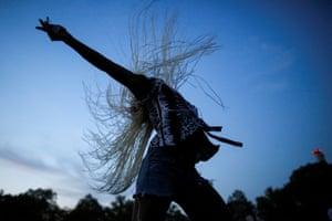 A woman dances at dusk