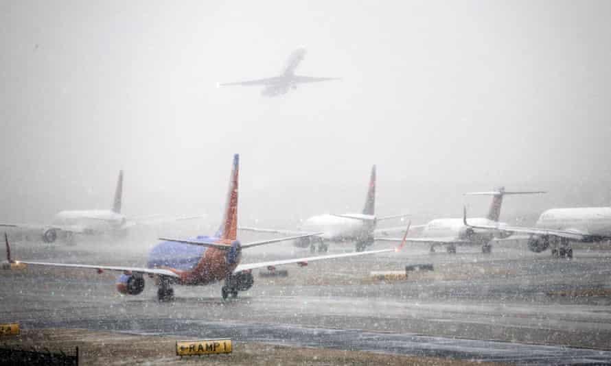 Planes line up on the tarmac as snow falls, delaying travel at Hartsfield-Jackson Atlanta International Airport in Atlanta.