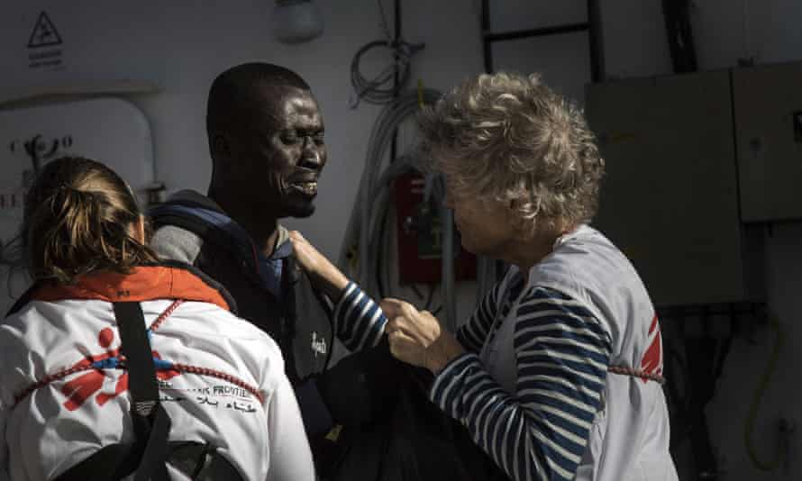 A migrant reacts as he is greeted by MSF workers aboard the Aquarius