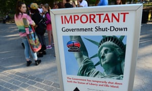 Tourists walk by a sign announcing the Statue of Liberty closure during the government shutdown in October 2013.