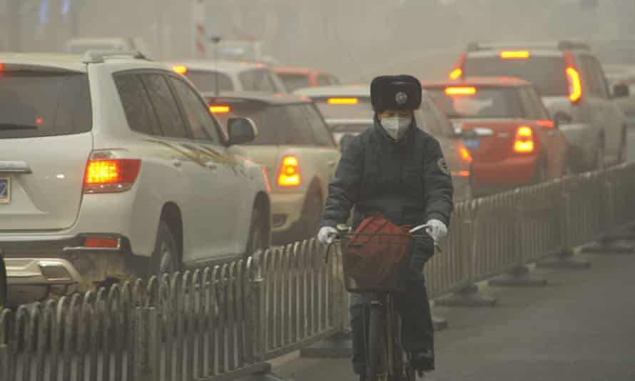 A cyclist wearing a face mask rides past cars on a road in heavy smog in Beijing. Coal power stations are a major contributor to the city's pollution.