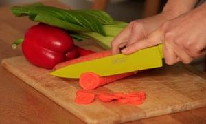 Hands chopping veg on a wooden board
