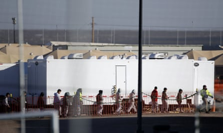 Migrant teens walk in a line through the camp in December.