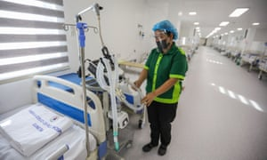 A worker cleans equipment inside a ward of a field hospital for Covid patients at a park in Manila on 24 June 2021.