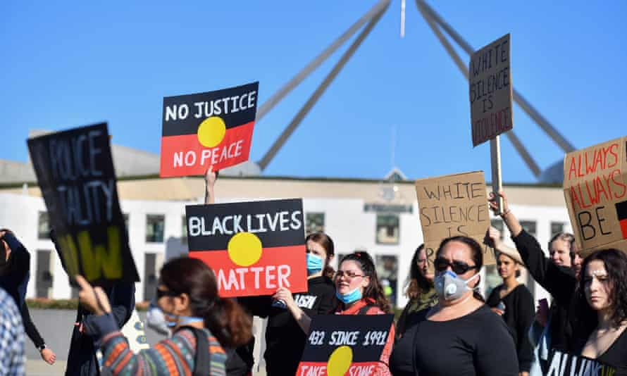 Black Lives Matter protesters hold placards outside parliament house in Canberra