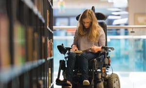 Young woman in a wheelchair in a library.