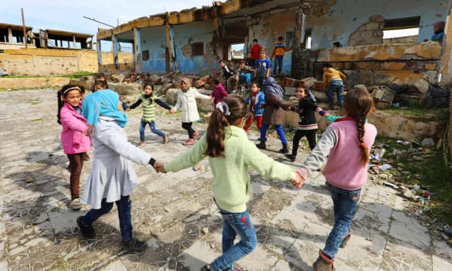 Children playing the shelled ruin of their school in western Idlib