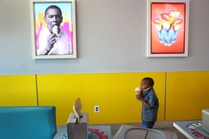 4-year-old Charistan Hood eats an ice cream near a picture of former President Barack Obama at the Ice Cream Heaven store in Miami Gardens on Blackout Day, when supporters commit to spending money only at black-owned businesses to showcase the economic power of the black community