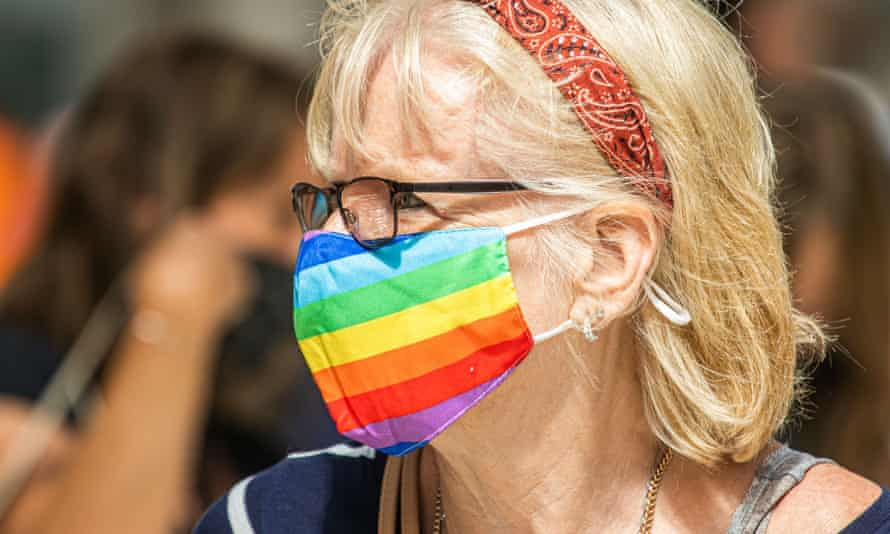 Woman wearing rainbow-striped face mask.