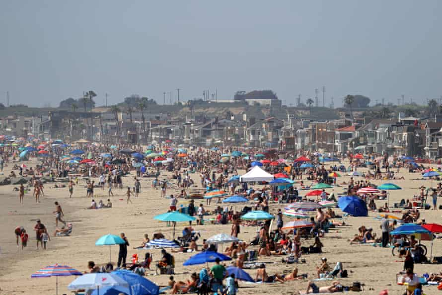People gathering on the beach north of Newport Beach pier on 25 April.