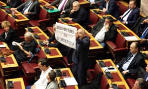 An MP holds a banner reading 'Don't blame Democracy' in parliament.