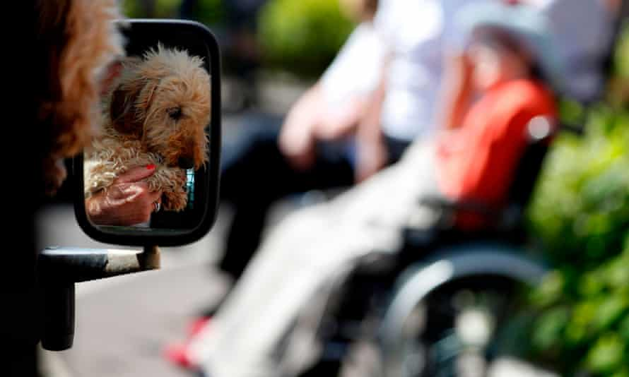 A woman shows her dog to her friend during a drive-through visit to a care home at the end of May.