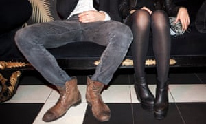 Young couple sitting side by side at night club with man's legs wide apart