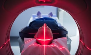 Male patient in medical scanner with red lights<br>Senior man lying down in scanning machine with red cross on head