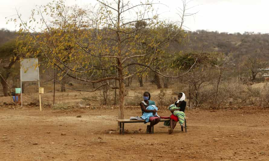 Women and babies wait to receive medical attention at a clinic on the outskirts of Harare