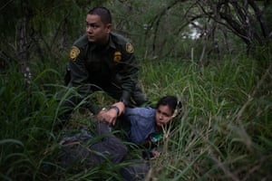A border patrol agent apprehends a woman after she was caught illegally crossing into the US from Mexico near McAllen.