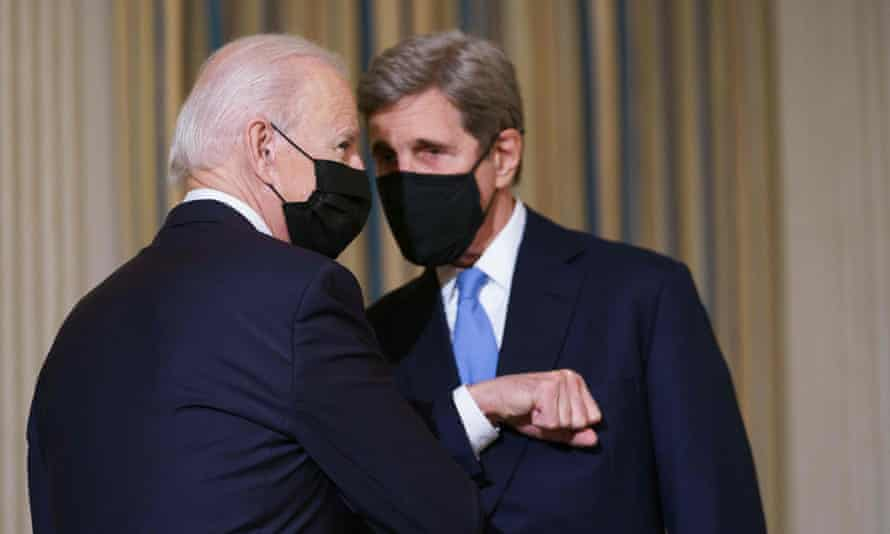 Joe Biden and his climate envoy, John Kerry, elbow bump during a meeting in Washington in late January.