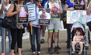 Asylum seeker advocates with their toddlers hold signs and pictures of babies of asylum seekers who face deportation after a high court ruling on offshore detention on Wednesday.